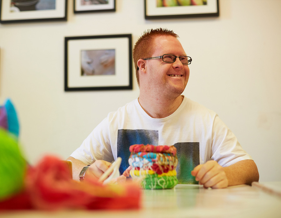 Smiling man with Down syndrome  at art table being creative