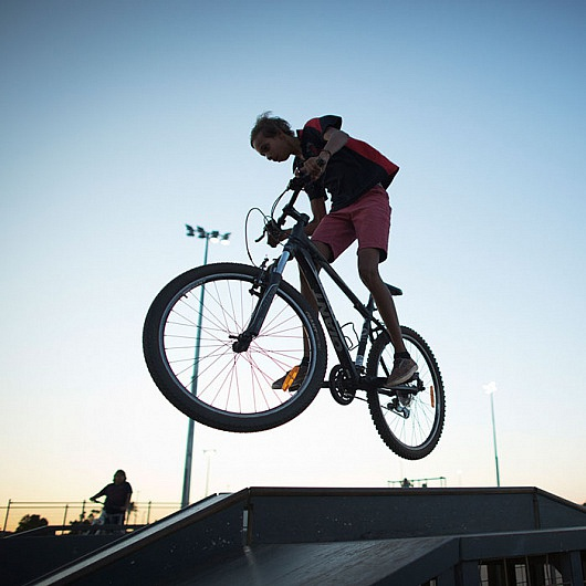 Young aboriginal kid getting air on a bike in a skate park