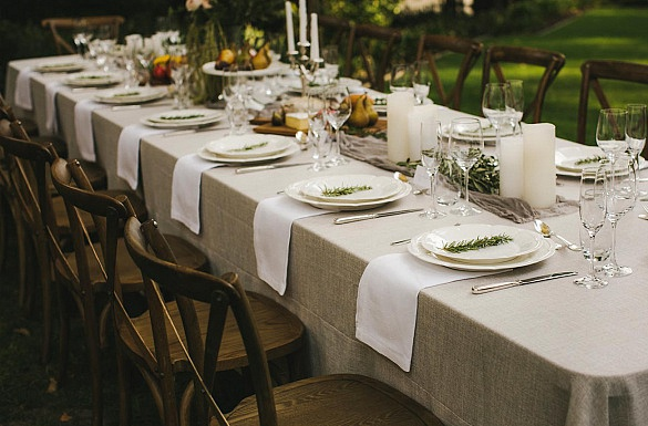 Media on Mars case study thumbnail: A long table set with full dinner service and beautiful natural flowers and linen