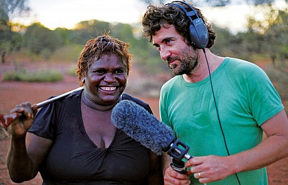 Media on Mars project thumbnail: White man in green t-shirt holding a big microphone interviewing an indigenous woman