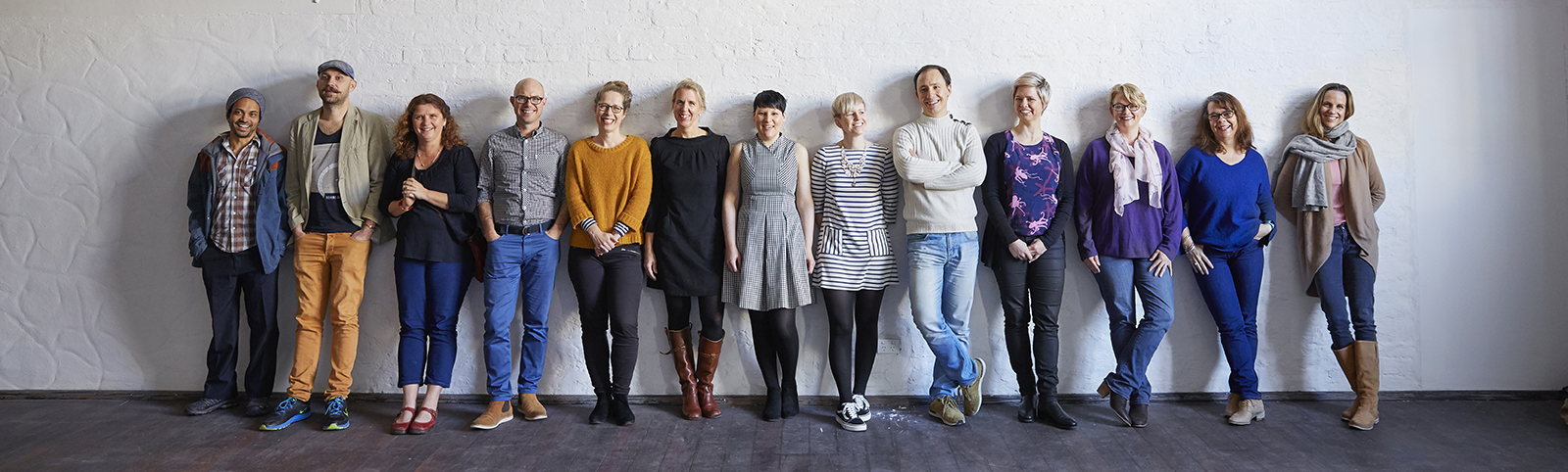 All staff leaning against a wall