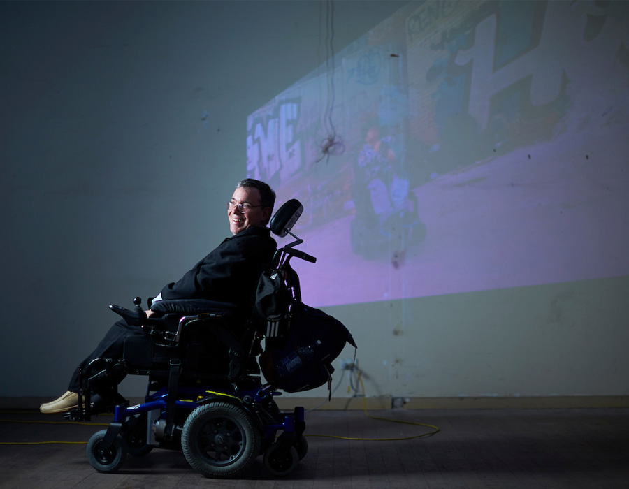 Male artist in wheelchair next to video installation projected on wall