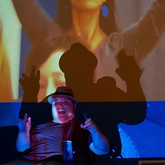 Young man in wheel chair in front of visual art projection