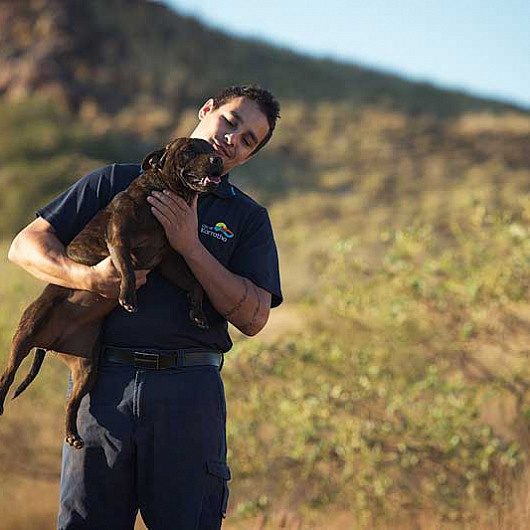 Ranger holding a dog in his arms