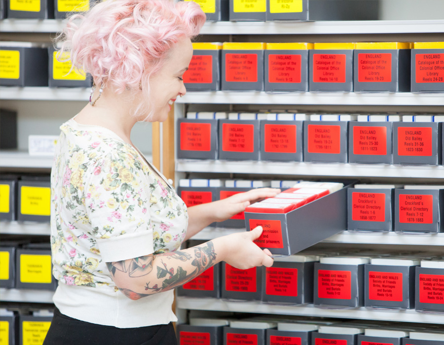 Young woman with pink hair and tattoos at library catalogue