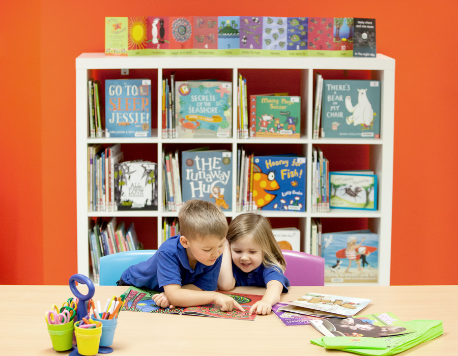 Two kids reading books in the book corner