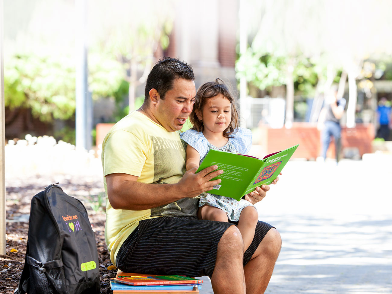 Man reading to a young girl outdoors