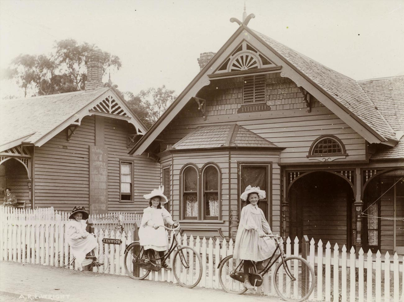Three girls from the early 20th century playing in front of a federation style cottage