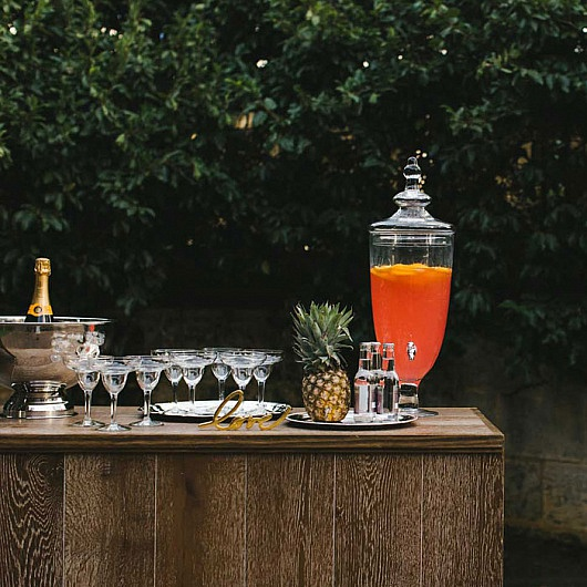 Rustic wooden bar out side with martini glasses and pitcher full of orangeade on top