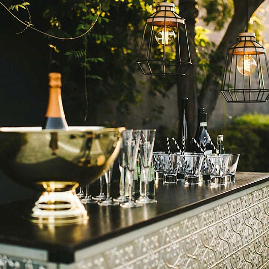 Outdoor bar with champagne and wirecage lanterns