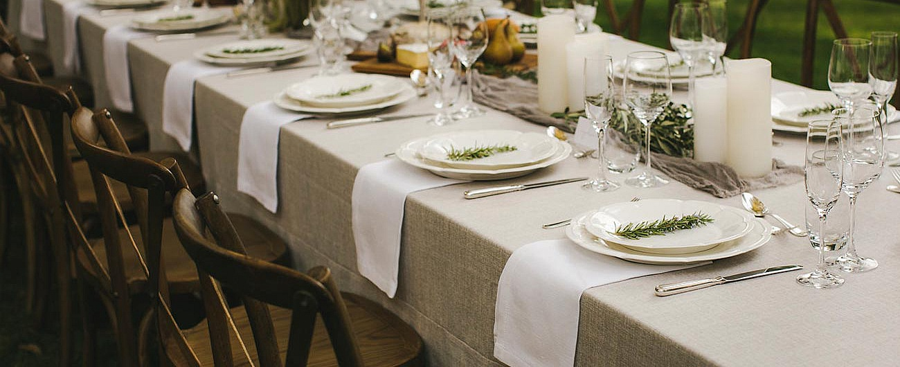 A long table set with full dinner service and beautiful natural flowers and linen