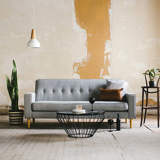 Large room with peeling paint on the walls, danish style couth with tastful cushions and coffee table