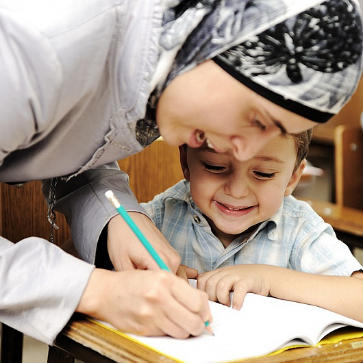 Young teacher in hijab teaching a little boy