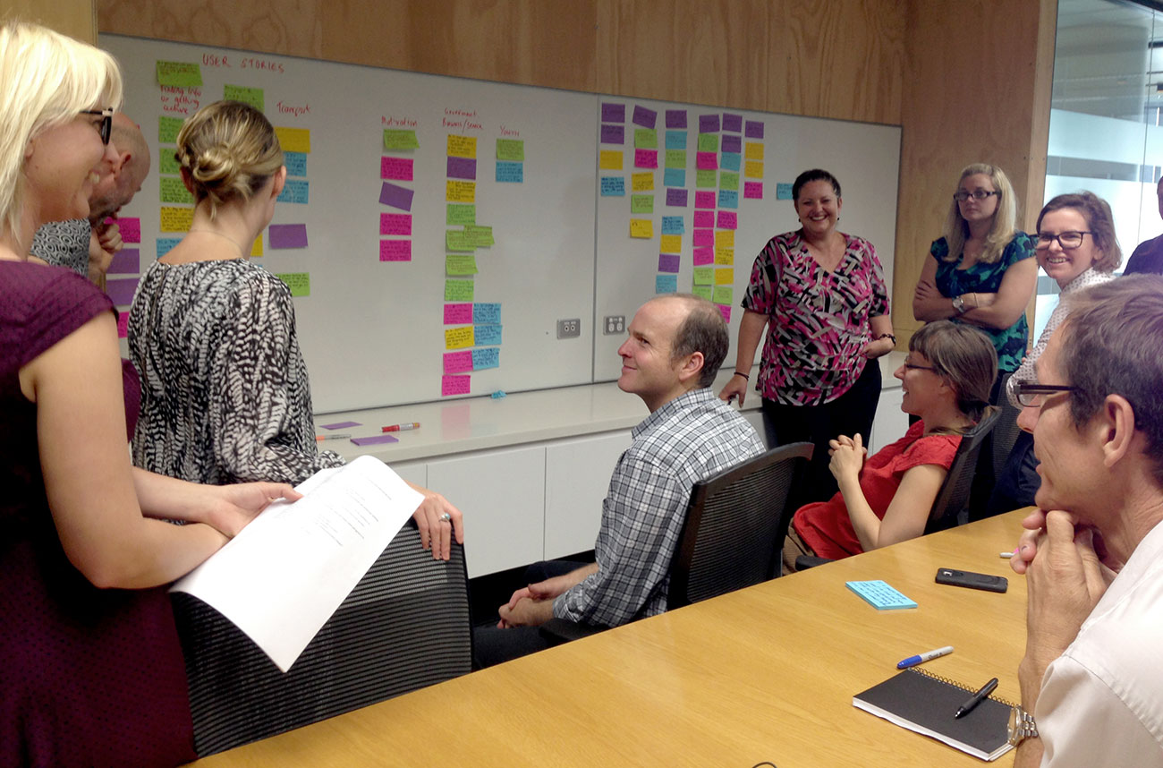 Group of people in a corporate boardroom having a discussion with a whiteboard and Postit notes