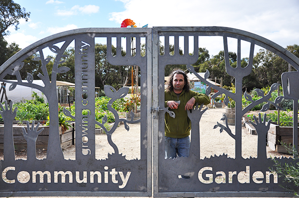 Man leaning against the gates of Busselton Community Garden