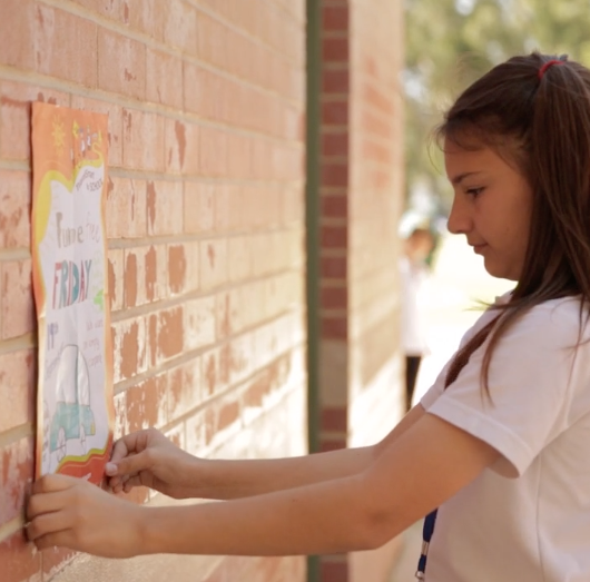 School student tacking poster to brick wall