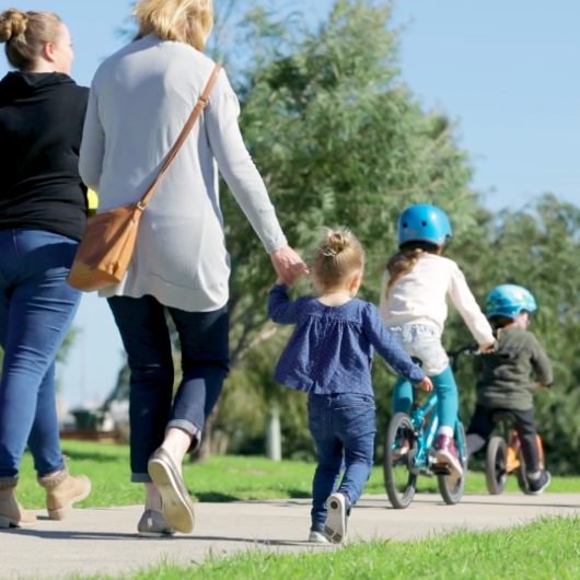 Two adult babysitters walk with children along a path