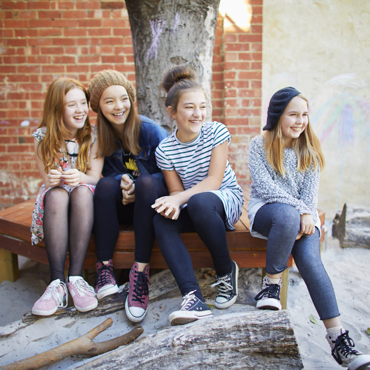 Four school girls sitting together smiling
