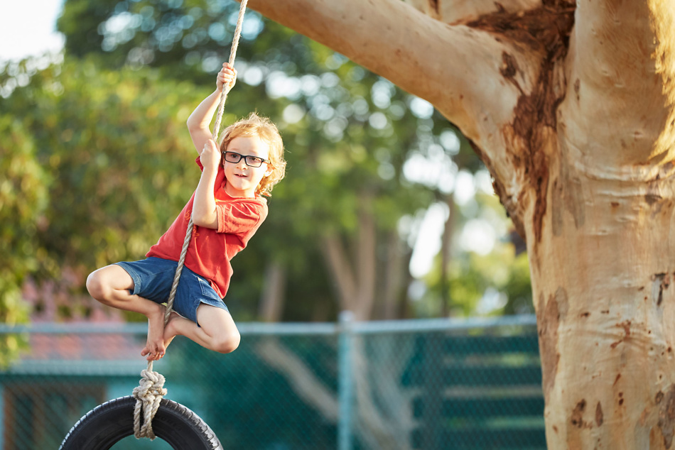 Young boy with glasses playing on tyre swing