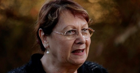 Middle aged woman with glasses talking to camera