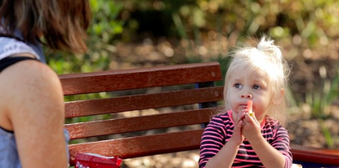 Young girl sitting on bench eating and looking at her mother