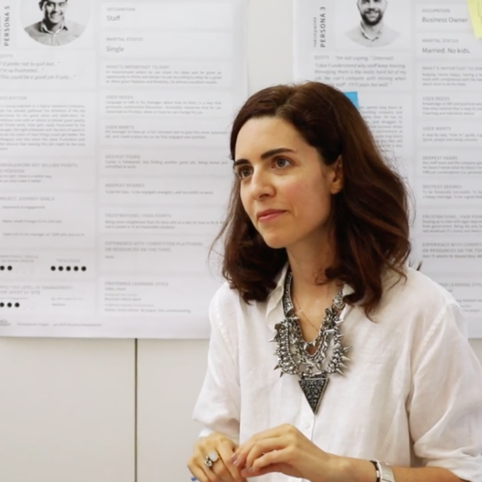 Woman stands in front of posters, directing a user focused design workshop
