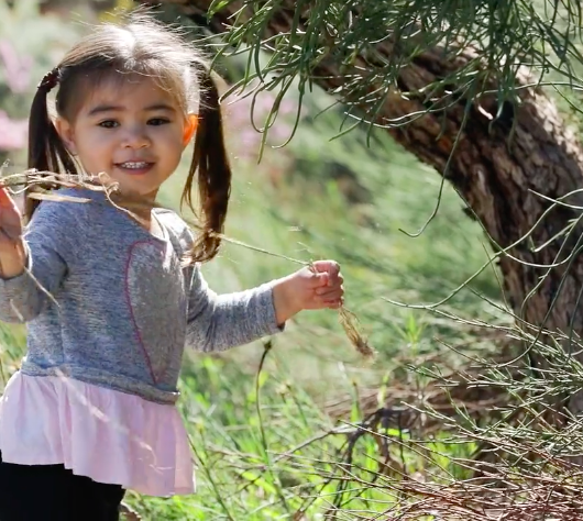 Young aboriginal girl playing in nature