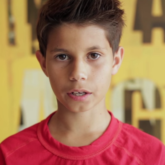 Young boy in red shirt talking to camera