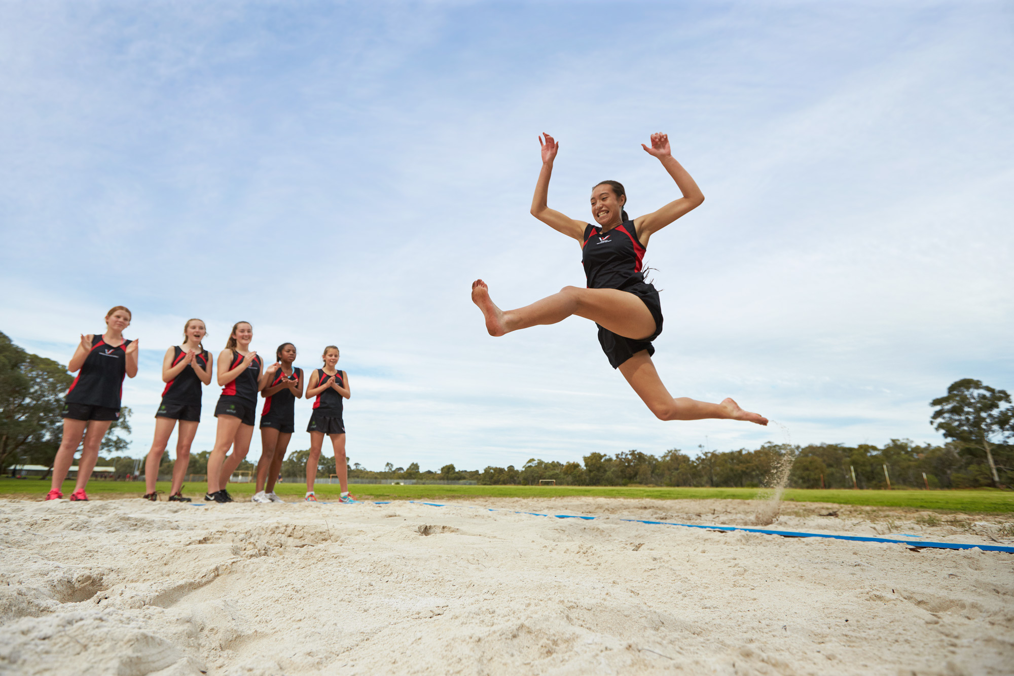 A Warwick Senior High School students participates in long jump while her peers watch and clap her on