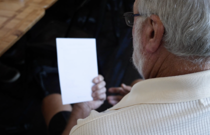 Media on Mars video thumbnail: Over the shoulder view of older man reading a small bar menu