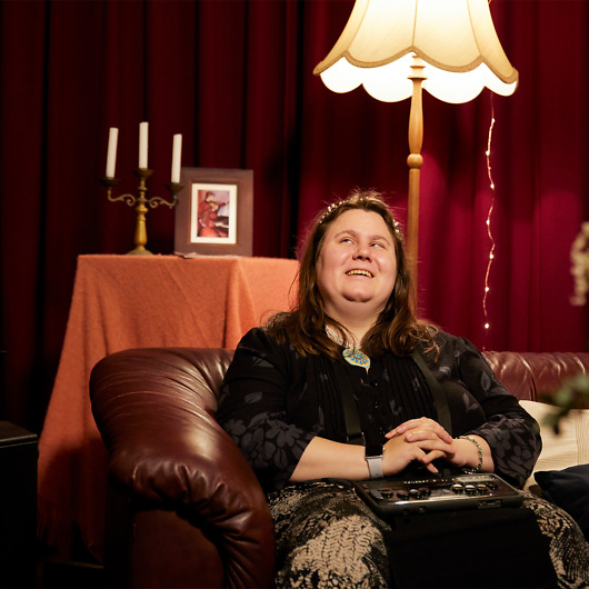 A blind woman sits on a brown leather couch in a plush, low-lit room decorated with red velvet curtains